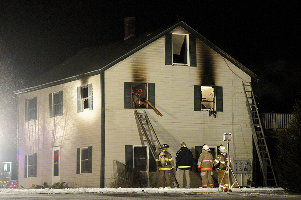 Firefighters battle a house fire on Town Farm Road in Hallowell on Thursday night.