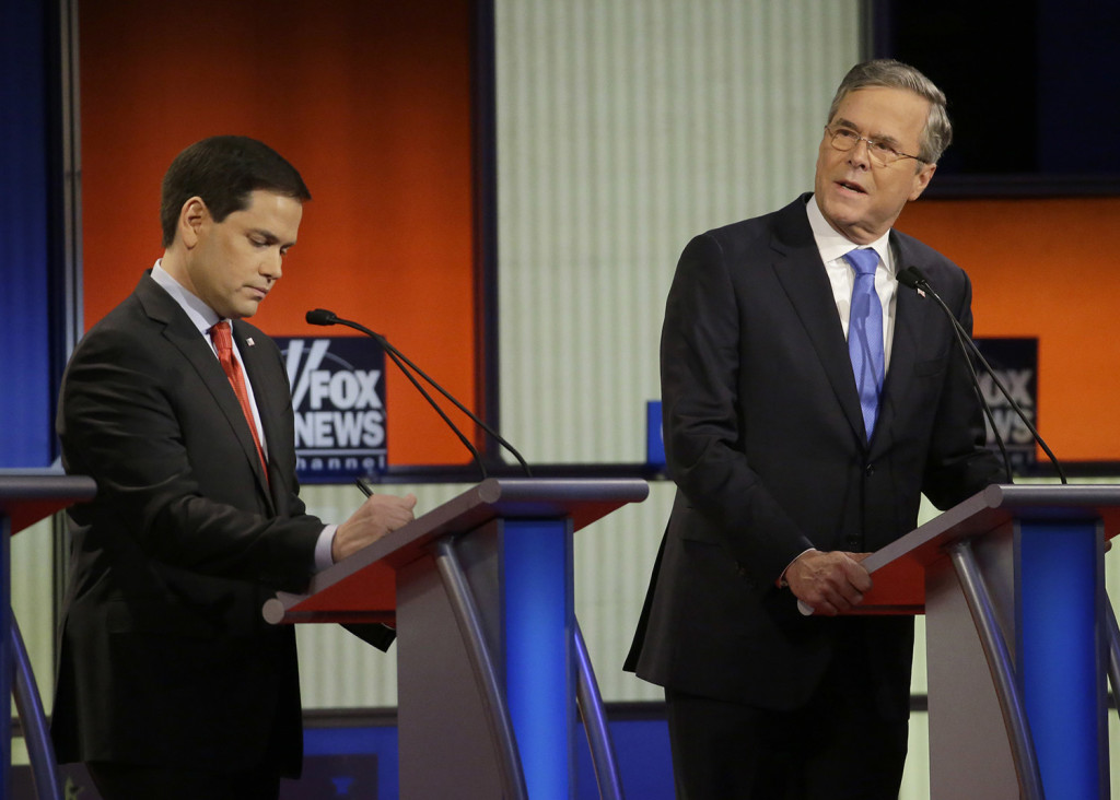 """Jeb Bush, right, talks as Marco Rubio listens during Thursday's debate. He said sarcastically, """"I kind of miss Donald Trump, he was a teddy bear to me."""" The Associated Press"""