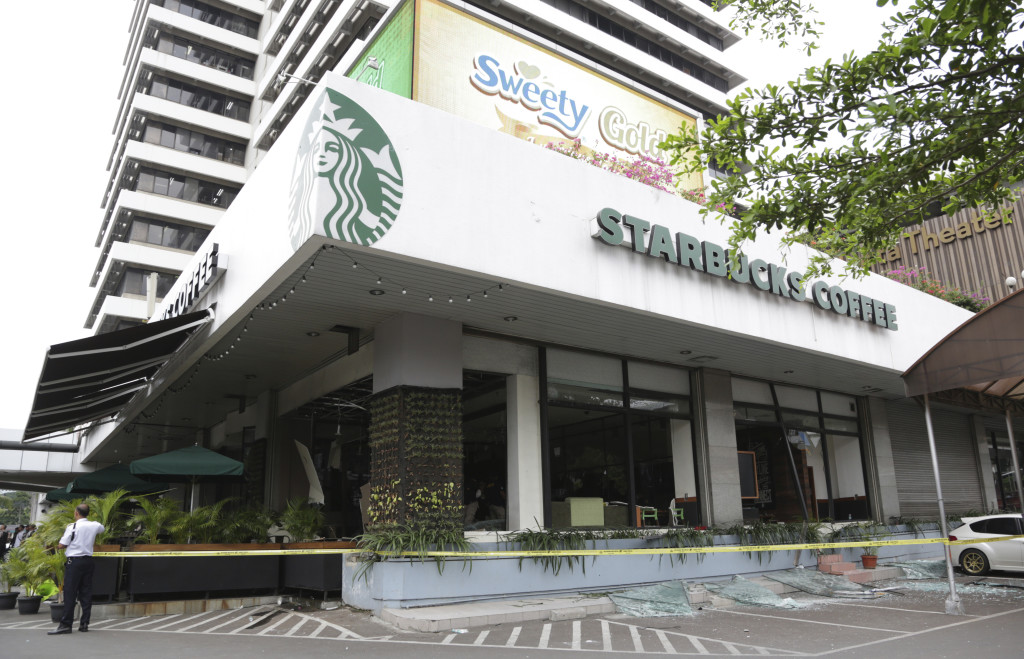 A damaged Starbucks cafe is cordoned off after an attack in Jakarta, Indonesia on Thursday. Attackers set off explosions at the cafe in a bustling shopping area in Indonesia's capital. The Associated Press