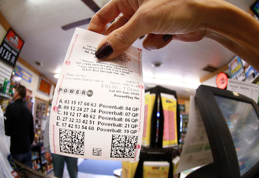 In this photo made with a fisheye lens a clerk hands a patron his $10 worth of chances for the upcoming Powerball drawing on Saturday. The Associated Press