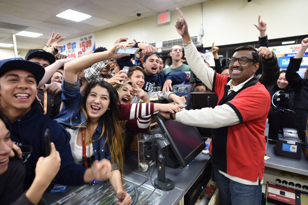 7-Eleven clerk M. Faroqui celebrates with customers Wednesday after learning the Chino Hills, Calif., store sold a winning Powerball ticket.  One winning ticket. Will Lester/The Sun via AP