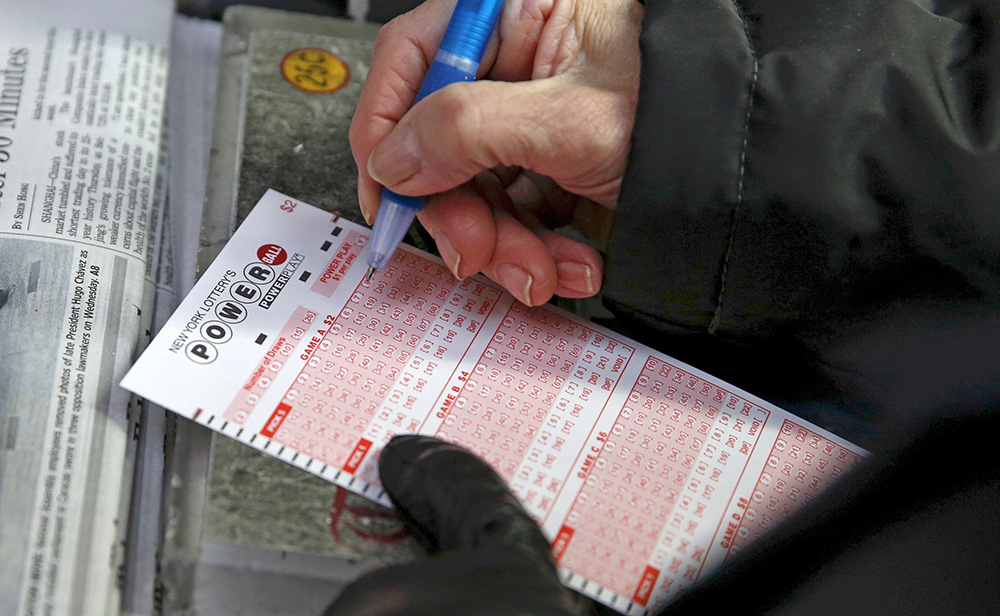 A woman fills out a ticket for the Powerball lottery in Times Square Thursday. Reuters