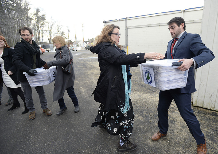 Campaign manager David Boyer passes a box of petitions to Rep. Diane Russell  from Portland as the Campaign to Regulate Marijuana Like Alcohol prepares to deliver the petitions to Augusta Monday, February 1, 2016.