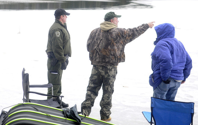 Game Warden Steve Allarie, left, checks ice fishermen Dennis Simard, center, and Marcel Chrissman on Lower Narrows Pond in Winthrop on Monday. With traps a few yards from open water, Allarie urged the anglers to exercise caution on the unseasonably thin ice.