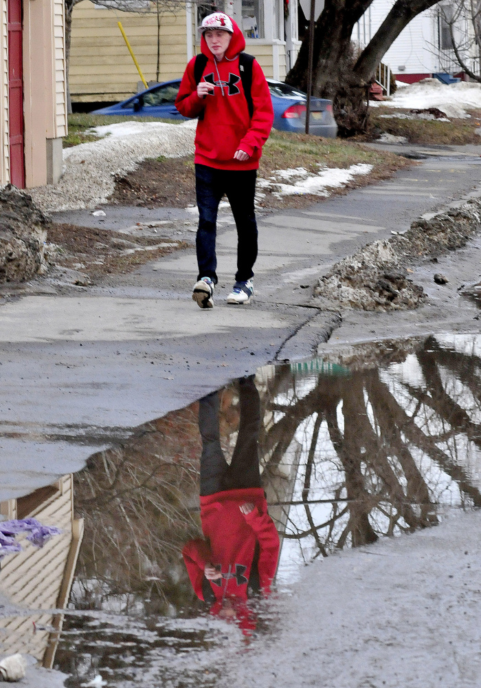 """Noah Burnham is reflected in water that is usually frozen this time of year while walking in Waterville on Monday. Asked his opinion on the recent warm temperatures Burnham said, """"I like it a lot."""""""