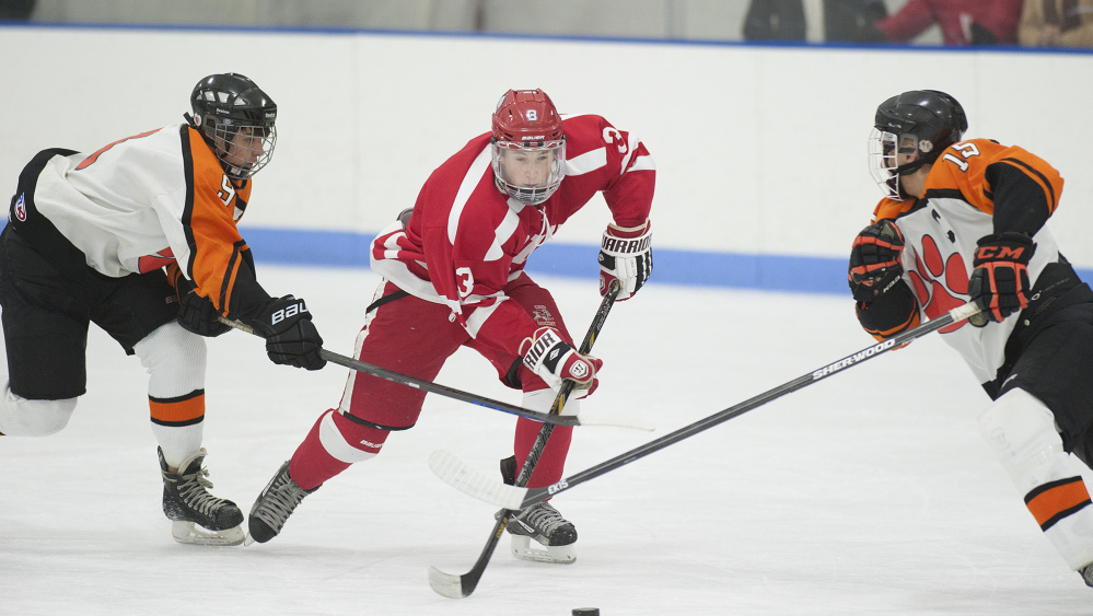 Cony forward Connor Perry, center, brings the puck down the ice during a game against Gardiner earlier this season at the Ice Vault in Hallowell.