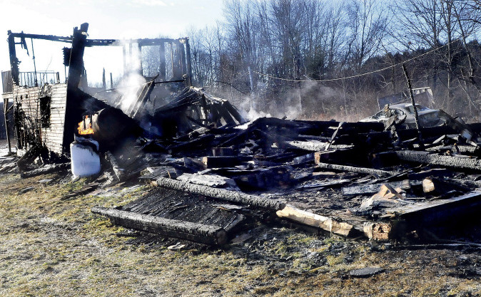 Smoke rises from the remains of a barn and vehicle that were destroyed by fire Monday. Gilbert Shaw, who lived in an apartment in the barn was treated for smoke inhalation. Flames can be seen coming from the top of a propane tank as it is vented.