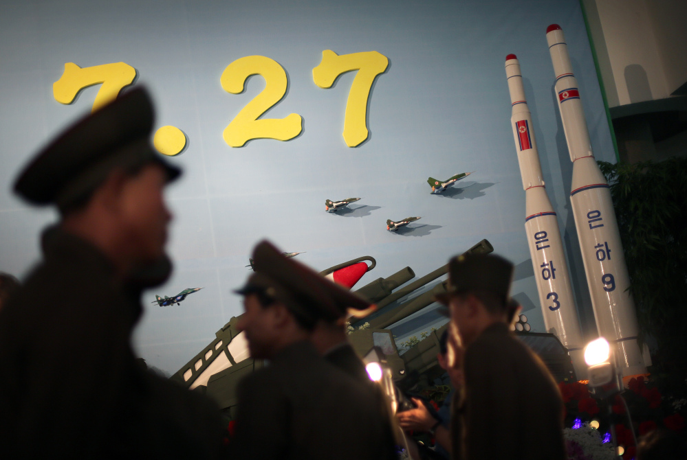 In this July 26, 2013, photo, North Korean soldiers are silhouetted against model versions of the Unha 3 space launch vehicle which successfully delivered North Korea's first satellite into Earth orbit, and the Unha 9, right, which would carry a lunar orbiter, on display at an annual flower show held in honor of national founder Kim Il Sung and his son Kim Jong Il, in Pyongyang, North Korea.