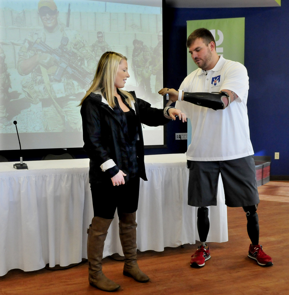 Travis Mills explains the use of his prosthetic devices to Thomas College Student Amanda Landry. Mills was the opening keynote speaker at the college's fourth annual Diversity Conference Tuesday.