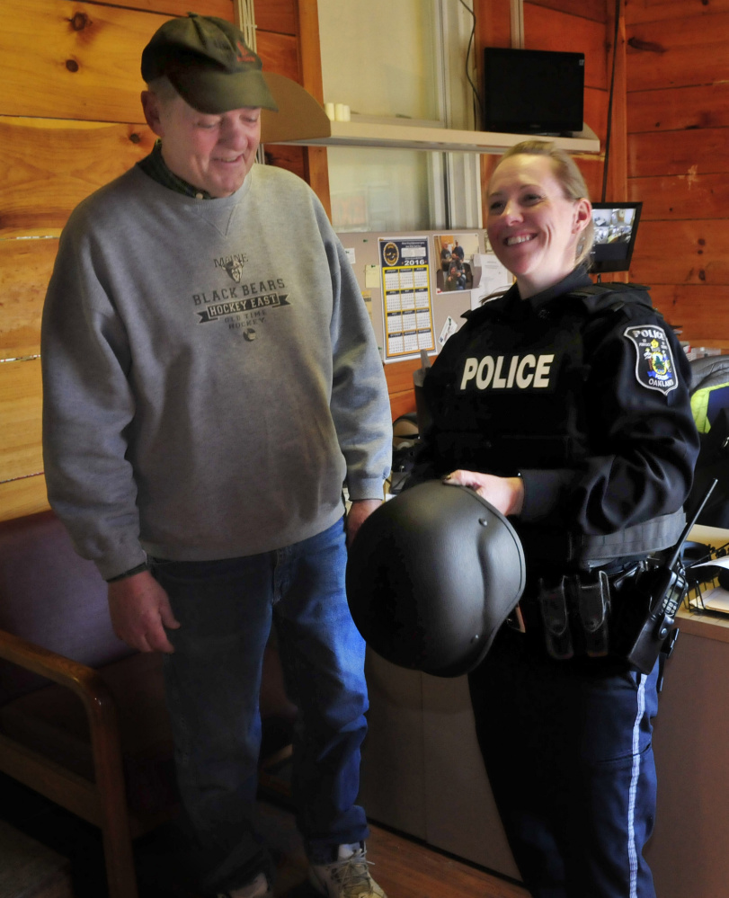 Oakland police officer Tanya Allen on Tuesday tries on one of four new ballistic vests and helmets that were donated to the department by area businessmen in the wake of the fatal shooting in town last November. The donors are Kevin Joseph, E. J. Fabian and Dave Libby, seen beside Allen.