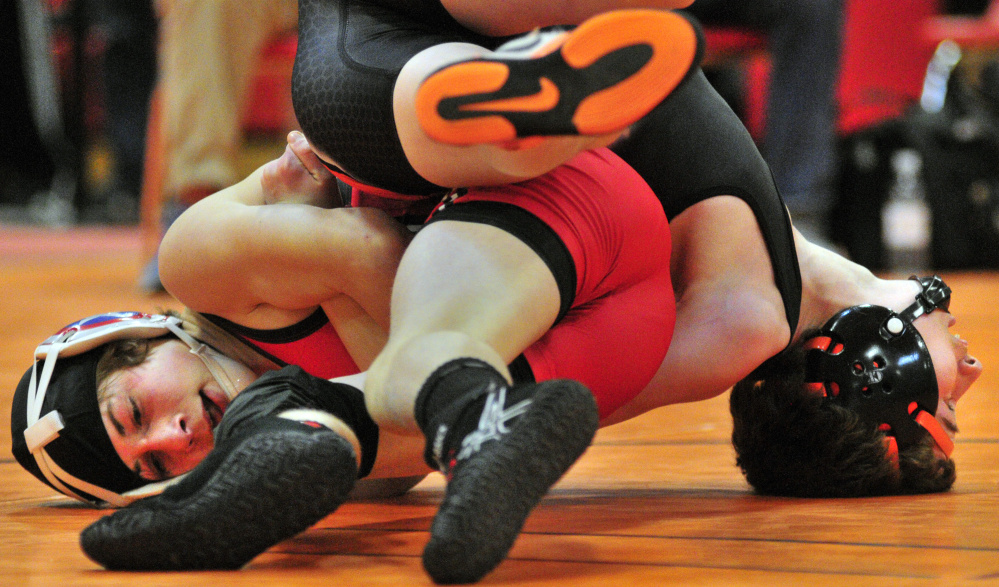 Cony's Noah Dumas, left, and Skowhegan's Austin Merrill compete in the semifinals of the 106-pound class during the Kennebec Valley Athletic Conference wrestling championships last Saturday afternoon at Cony High School. Dumas won the match and would go on to take the title.