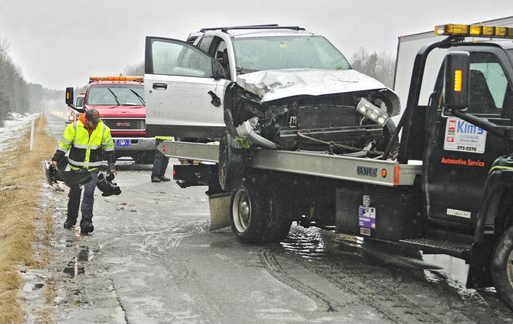 A tow truck driver carries broken vehicle pieces to throw onto the flatbed with a wrecked Saturn Vue around 1:45 p.m. Wednesday along northbound lanes of Interstate 95 near the Town Farm Road overpass in Sidney. The accident was among several Wednesday following periods of freezing rain.