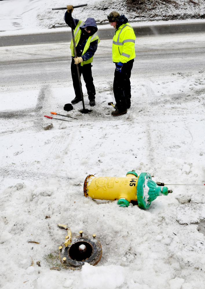 Ryan Adams, left, and Tony Bellavance, of the Kennebec Water District, repair a fire hydrant that was knocked over by a driver whose vehicle slid off North Street as snow covered the road on Wednesday. Adams said the hydrants are designed to break away and limit damage.