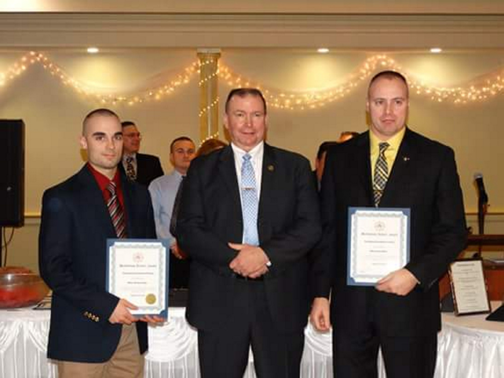 Farmington police officers Michael Lyman, left, and Darin Gilbert, right, receive a Meritorious Service Award from Maine Association of Police President Kevin Riordan, center, at the MAP awards banquet last week. The two Farmington officers were recognized for helping to find a missing New Hampshire boy who was allegedly abducted by his father in July.