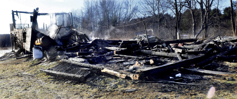 Smoke rises from the remains of a home and vehicle that was destroyed by fire Monday. The cause is undetermined the fire chief said Thursday.