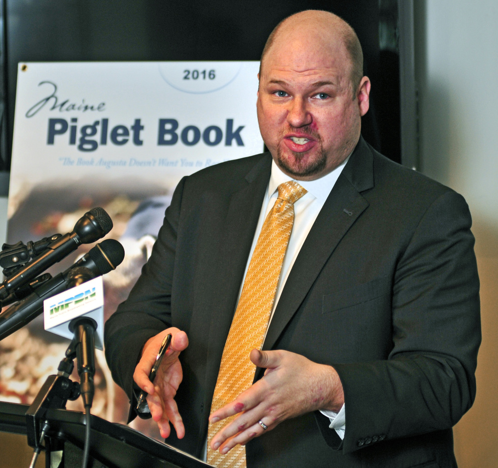 """Matthew Gagnon of the Maine Heritage Policy Center talks about the 2016 Maine Piglet Book during a news conference Thursday at the State House Welcome Center in Augusta. In a news release, the policy center said that the booklet """"highlights the rampant and appalling examples of the abuse of taxpayer dollars that big government doesn't want you to know about."""""""