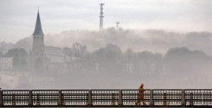 St. Augustine Church can be seen through the mist Thursday as a person walks over the Calumet Bridge at Old Fort Western above the fog-shrouded Kennebec River in downtown Augusta.