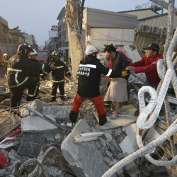 Rescue workers guide a man from the rubble of a toppled building after an earthquake in Tainan, Taiwan, Saturday.