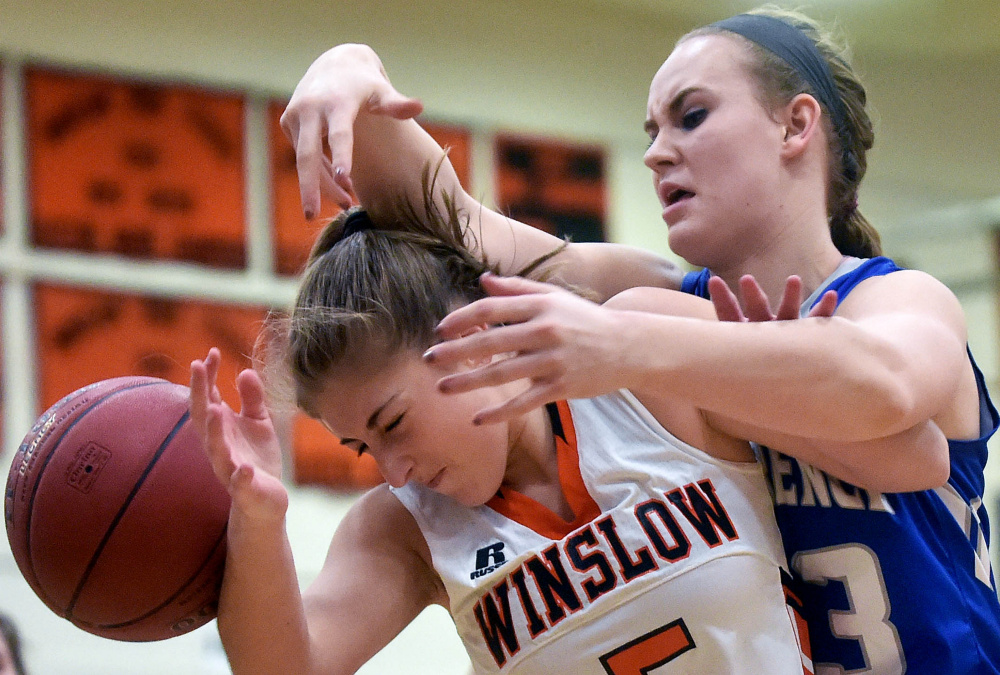 Winslow's Brogan Gagnon, front, and Lawrence's Nia Irving battle for a rebound during a Kennebec Valley Athletic Conference game earlier this season.
