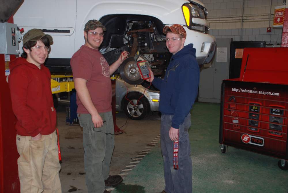 """From left, Gregory Shrader, of Canaan; Owen Boardman, of Cornville; and Aaron Noonan, of Pittsfield, are learning how to measure wheel speed sensor signals on the Chevrolet Trailblazer, one of three vehicles donated to Somerset Career and Technical Center in Skowhegan by General Motors Company and the GM Automotive Service Education Program at Lakes Region Community College in Laconia, N.H. The GM vehicle donation program supports automotive technical education at high school career and technical centers and community colleges throughout New England. Receiving programs must be accredited by the National Automotive Technical Education Foundation. Automotive instructor Mark Wilson, who recently received the three vehicles that students will hone their service and diagnostic skills, said, """"These students are learning how to use the Snap On meter at the same time they are developing an understanding of the inputs used to make the GM anti-lock braking system work. The meter training the students receive prepares them to pass an examination which earns them Snap On Meter Certification. The use of these donation vehicles will provide our students the opportunity to learn about the systems they will be diagnosing and servicing in the workplace. We are very pleased to receive these vehicles and will make good use of them."""""""