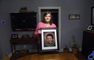 Hollie Ayers poses with a photograph of her late son, Michael, 2, at her home in Bedford, Pa., on Jan. 18. Michael, was shot and killed in front of her by her abusive ex-husband in 2013. Ayers was shot in the face and the leg, and her ex-husband killed himself after the rampage. More than a dozen states over the past two years have strengthened laws meant to keep firearms out of the hands of domestic abusers, a rare area of consensus in the nation's highly polarized debate over guns.