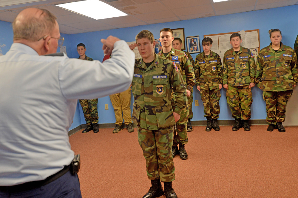 Commander Roger Sabourin, left, salutes Cadet Paul Southwick, center, after he received the Civil Air Patrol's Wright Brothers Award at Robert LaFleur Municipal Airport in Waterville on Thursday.