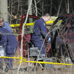 Maine State Police detectives examine the SUV containing the bodies of Eric Williams and Bonnie Royer, who were found dead on Sanford Road in Manchester early Christmas morning.