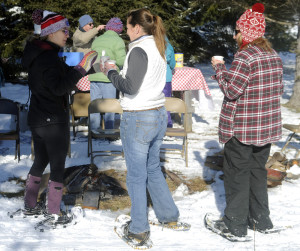 People warm up Sunday next to a fire at Viles Arboretum in Augusta during the Table Tour fundraiser.