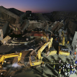 As night falls, emergency rescue workers continue to search the rubble of a collapsed building complex in Tainan, Taiwan, Monday.