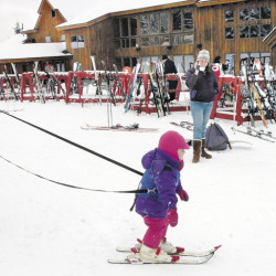A child is held by a tether line by her father while skiing for the first time near the base lodge at Saddleback ski resort near Rangeley in March 2009 . Owners say the resort will not open in time for the February school vacations later this month.