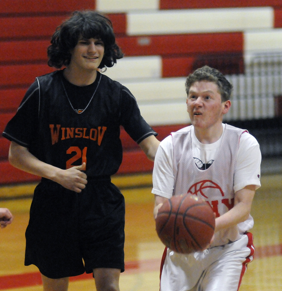 Cony High School's Aaron Gray looks for an opening around Winslow defender Dakota Land during a unified basketball game Monday in Augusta.
