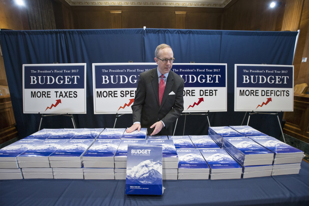 Copies of President Barack Obama's final fiscal 2017 federal budget proposal are staged for display by Eric Euland, Republican staff director for the Senate Budget Committee, Tuesday on Capitol Hill in Washington.