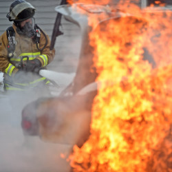 Lt. Rocque, with the South China Volunteer Fire Department, attempts to extinguish a car fire on Windsor Road in South China on Tuesday.