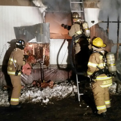 Firefighters hose down a mobile home that erupted in flames early Saturday morning on Webb Road in Oakland.