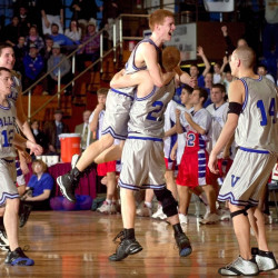 Valley High School's Luke Hartwell leaps into brother Jason's arms after the Cavaliers won their fifth consecutive state championship in Augusta on March 3, 2002. Brian Andre, in background, Chris Atwood (12) and Lucas Melcher (14) join the celebration.