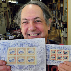 Robert Sezak holds copies of two versions of postage stamps on Nov. 9. The copies at left show a Jenny aircraft in the upright flying position, which fetched $50,000 when auctioned at Julia's Auctions in Fairfield recently. In the 2.2 million-stamp run, 100 of the upright Jenny were included.