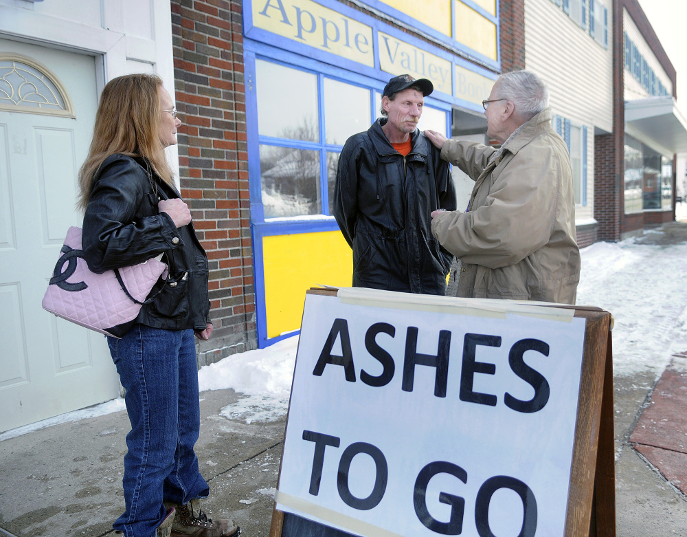 The Rev. James Gill speaks with Don Ladson Wednesday after applying ashes to him and Lori Audette on Main Street in Winthrop.