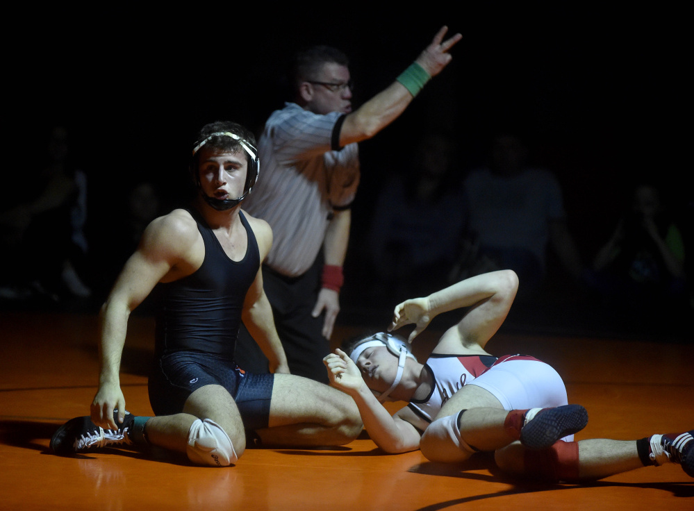 Skowhegan Area High School's Kameron Sirois, left, receives two points against Camden Hills High School's Eli Smith, right, in the 160-pound class in the regional finals Saturday in Skowhegan.