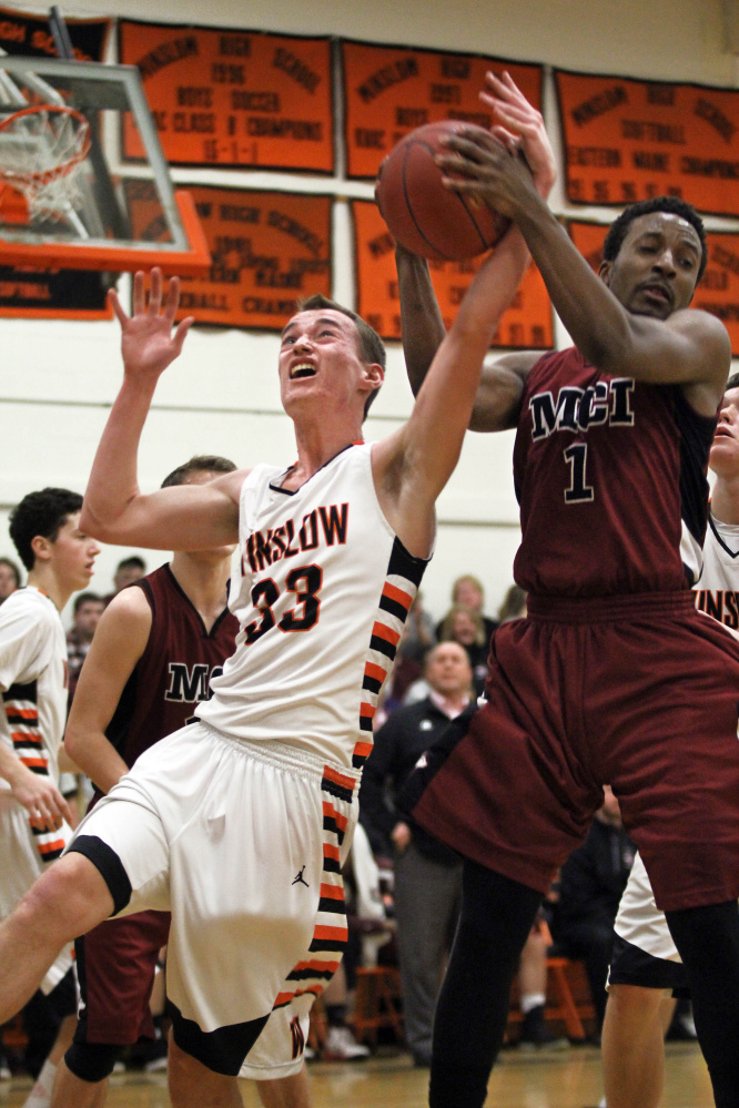 Winslow High School's Justin Burgher (33) battles for a rebound with Maine Central Institute's Tre Grier during the first half of a Class B North preliminary playoff game Wednesday in Winslow.