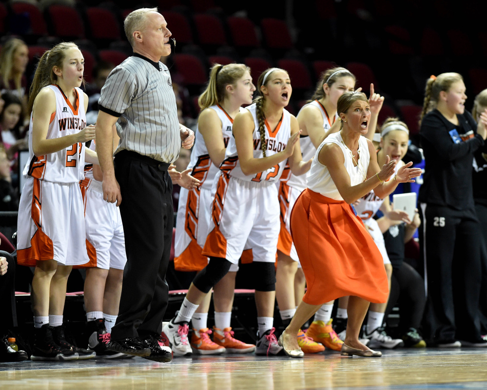 Winslow head coach Lindsey Withee and several players celebrate a basket during a Class B North quarterfinal Saturday against Ellsworth at the Cross Insurance Center in Bangor. Winslow won 51-44.