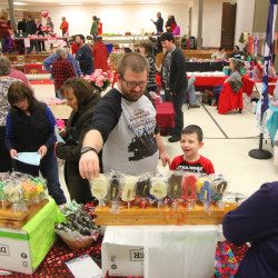 Cody Dow, of Benton, helps his 6-year-old son, Max, pick out a treat from Terry Fouquette's offerings Saturday at the annual Fairfield Chocolate Festival. Fouquette owns Terry's Country Candies, of New Gloucester. The event, held in the Fairfield Community Center, raised money for the Fairfield Council of Churches Emergency Heating Fund.