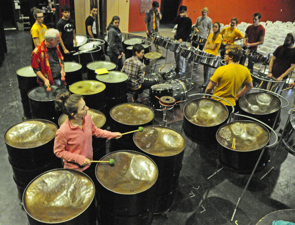 Zephyr Martin, bottom left, and other members of the Pan Planet band work with Kents Hill School students Saturday in a steel drum class during the International Festival at the school in Readfield.