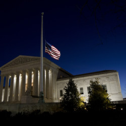 An American flag flies at half-staff in front of the U.S. Supreme Court building in honor of Supreme Court Justice Antonin Scalia as the sun rises in Washington, Sunday.
