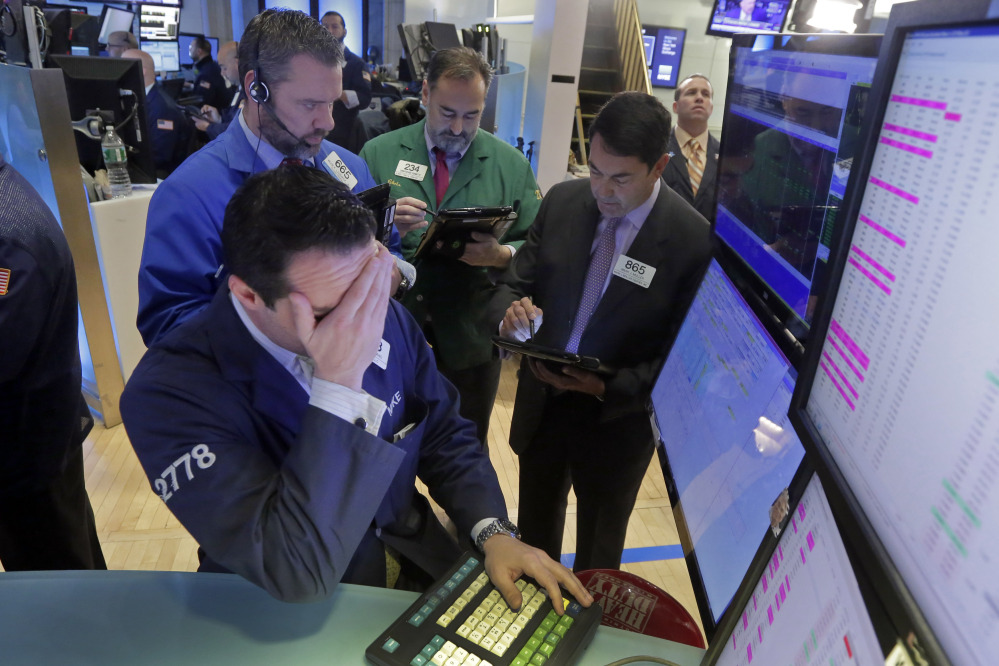 In this Feb. 1, 2016, file photo, specialist Michael Gagliano, foreground, works with traders at his post on the floor of the New York Stock Exchange.