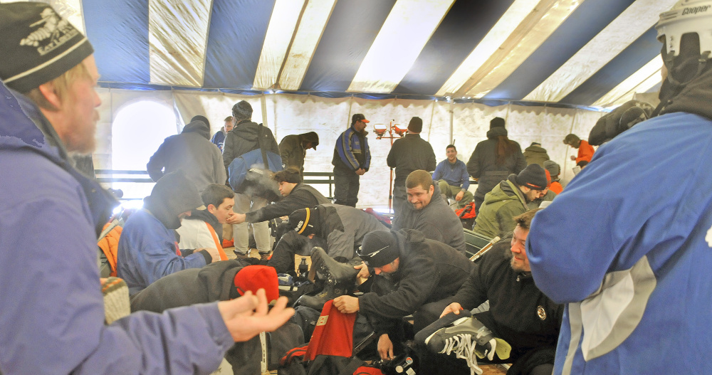 Players warm up and change Sunday under a tent during the Maine Pond Hockey Classic at the Snow Pond Center for the Arts in Sidney.
