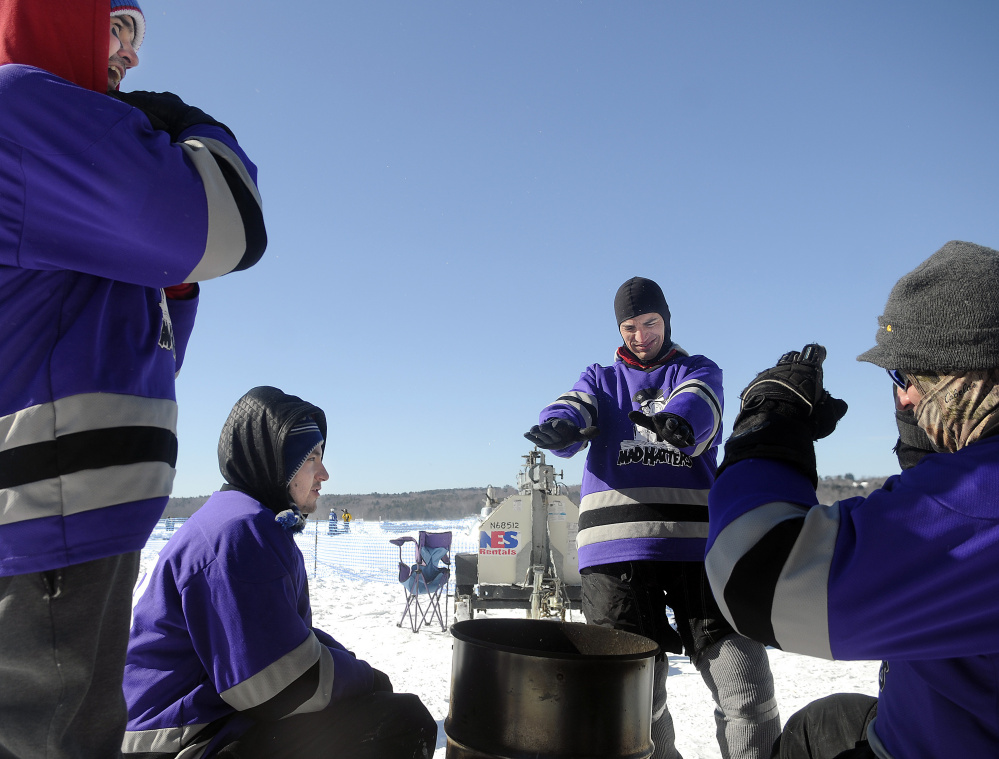 The Mad Hatters, of Portland, warm up Sunday in front of a fire during the Maine Pond Hockey Classic at the Snow Pond Center for the Arts in Sidney.