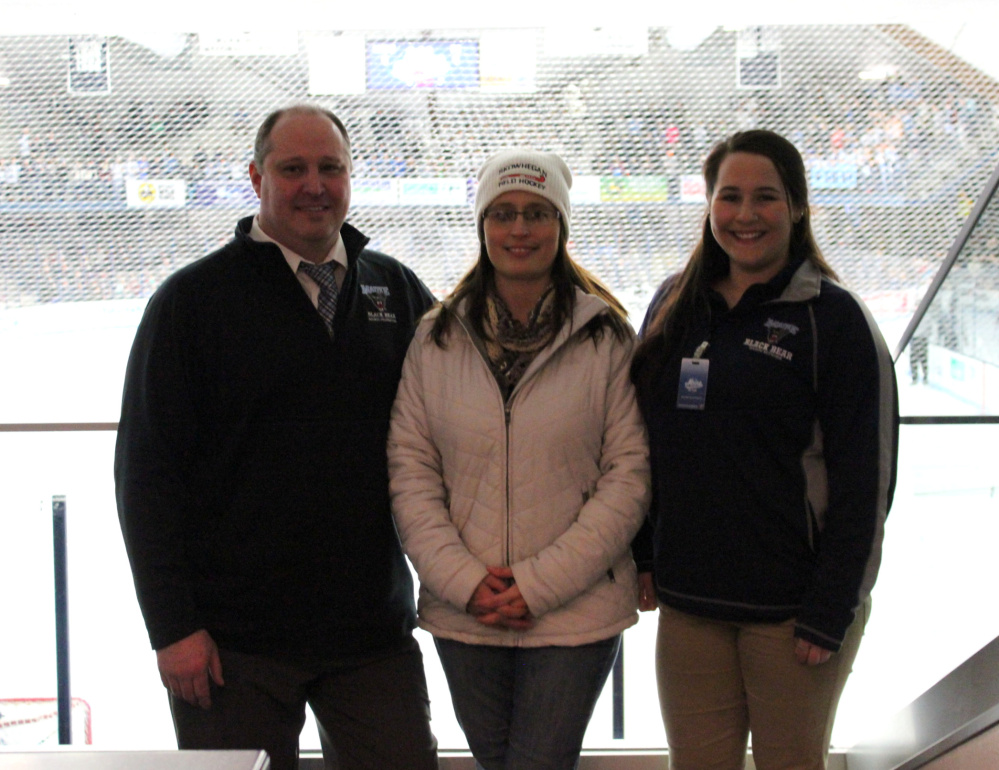 Holly Thebarge, center, of Smithfield, recently won a social media giveaway of University of Maine hockey tickets hosted by Sullivan Tire and Auto Service and UMaine. At the game, she meets with Jason Hoyt, Black Bear Sports Properties, left; and Jill Tuell, Black Bear Sports Properties.