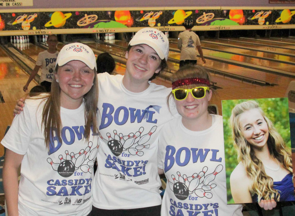 "Jordyn Labrie, Paige Smith and Gabi Martin, members of the Central Maine United soccer team, hold a photo of their friend and former teammate Cassidy Charette at last year's first ""Bowl for Cassidy's Sake"" that raised $50,000 for the Messalonskee school-based mentoring program. This year's event, on May 7th at Sparetime Recreation in Hallowell, will raise funds for a new program at the Alfond Youth Center in Waterville."