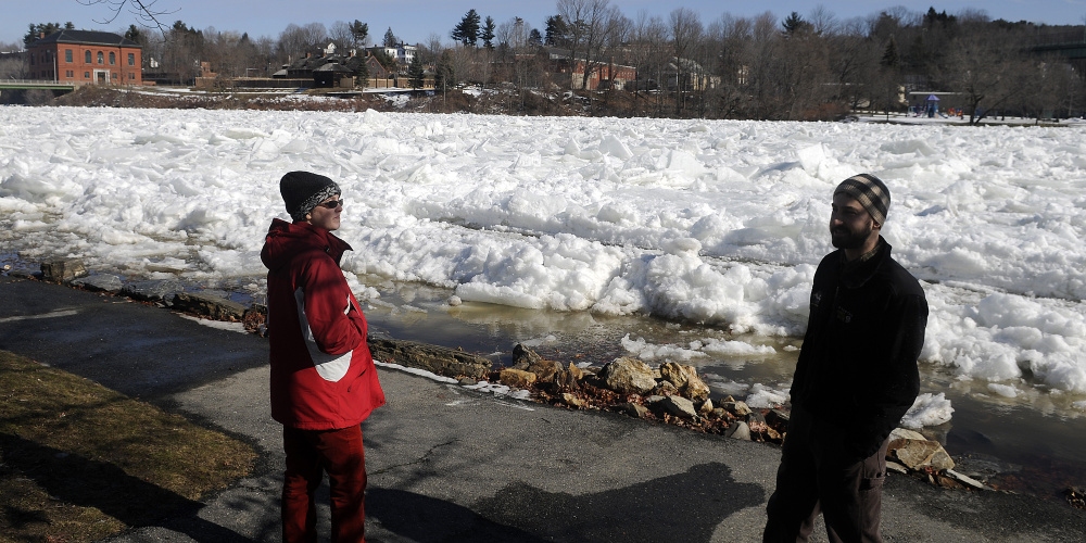 Amber Whittaker, left, and Ryan Gordon of the Maine Geological Survey examine Wednesday the ice jam on the Kennebec River in Augusta. Gordon, a hydrogeologist, said flooding occurs annually along the river corridor.