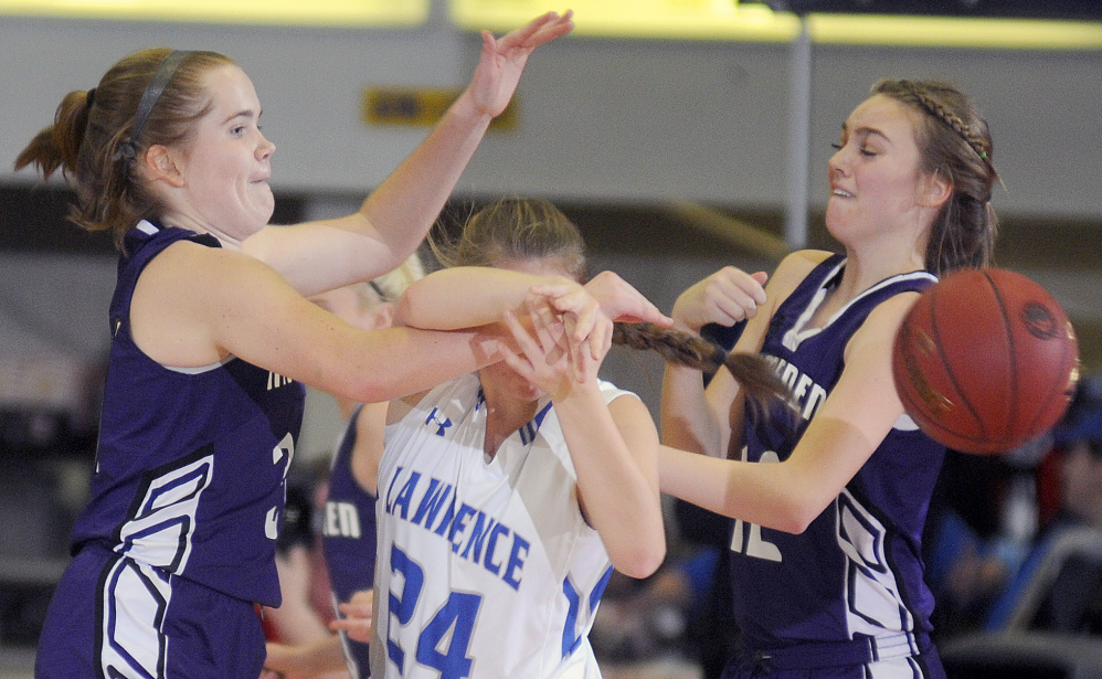 Lawrence's Molly Folsom draws heavy pressure from Hampden Academy's Peyton Smith, right, and Courtney Dunton during a Class A North semifinal Wednesday night at the Augusta Civic Center.